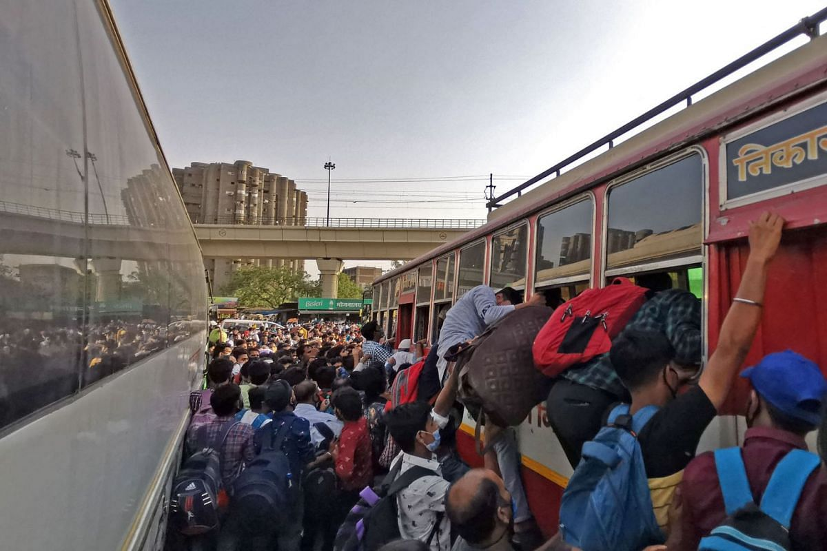 People rush to board their buses before a week-long lockdown ordered by the Delhi government comes into effect on April 19, 2021.