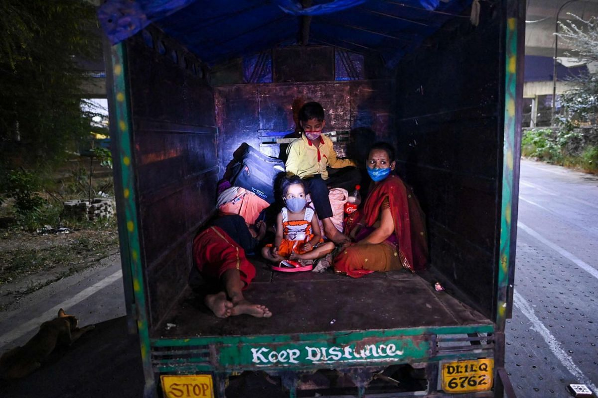A family sits in a truck at a bus station in New Delhi on April 19, 2021.