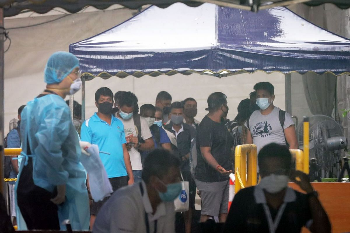 Workers wait to move out of Westlite Dormitory Woodlands on April 22, 2021, due to a Covid-19 outbreak.