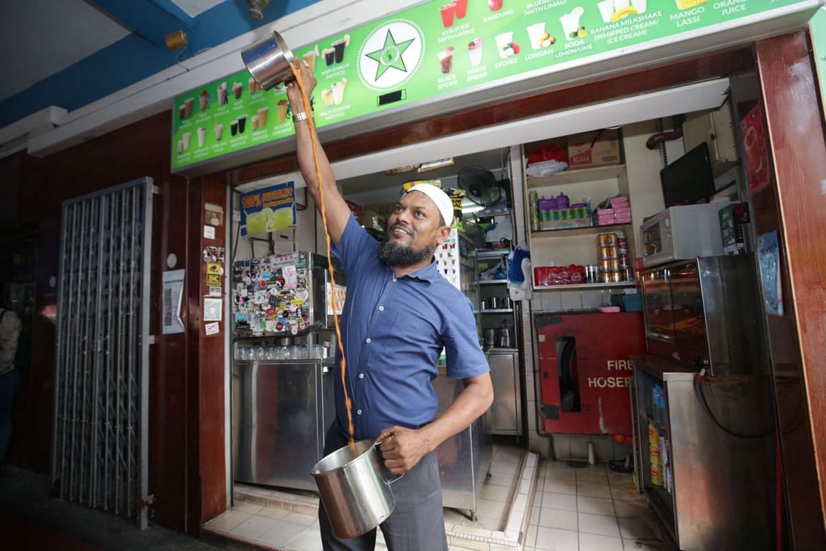 """Mohammad Asgar, owner of Bhai Sarbat Singapore demonstrating how he makes teh tarik on April 22, 2021. Seven new """"mini-museums"""" are popping up in the Kampong Glam area in front of shops that are notable for their distinctive history and practices"""