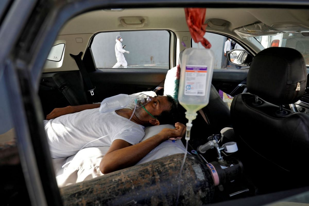 A patient with breathing problems lies inside a car while waiting to enter a COVID-19 hospital for treatment, amidst the spread of the coronavirus disease in Ahmedabad, India, April 22, 2021.