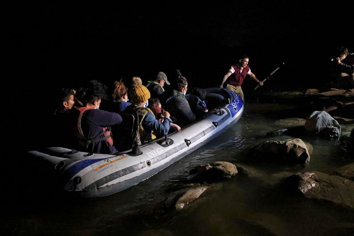 Asylum-seeking migrant families arrive on an inflatable raft after crossing the Rio Grande river into the United States from Mexico, in Roma, Texas, U.S., on April 21, 2021.