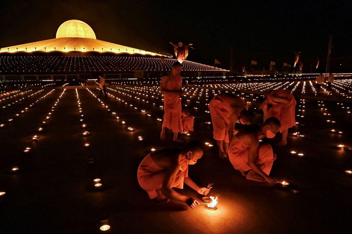Buddhist monks light 330,000 candles in an attempt to break the Guinness World Record for the largest flaming image during Earth Day celebrations at the Wat Dhammakaya Buddhist temple on the outskirts of Bangkok on April 22, 2021.
