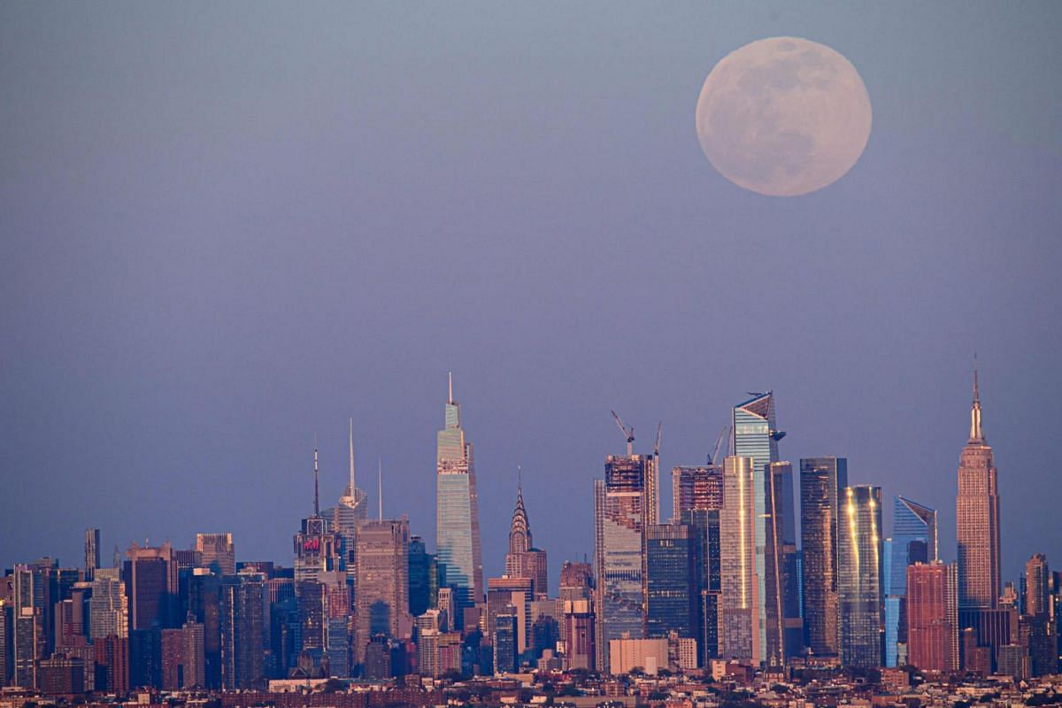 The supermoon rises over the skyline of Manhattan on April 26, 2021.