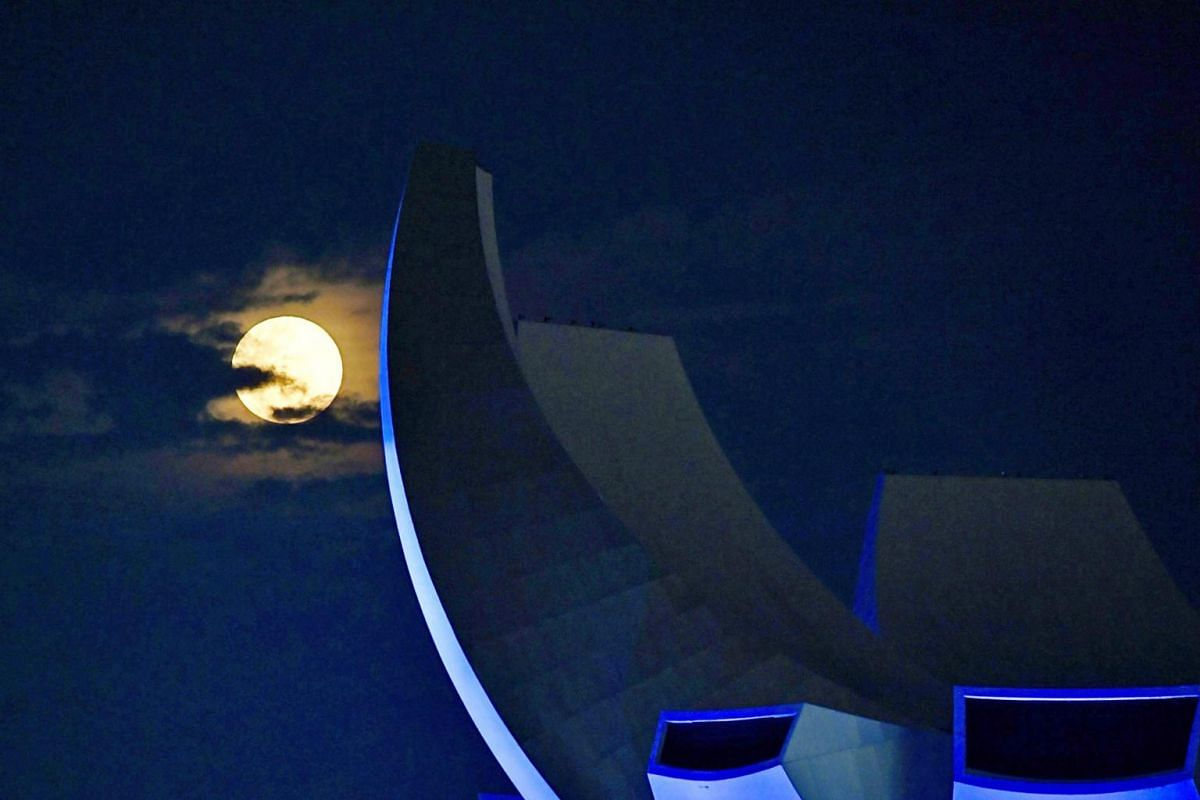 The pink moon rising behind the Art Science Museum at Marina Bay Sands on April 27, 2021.