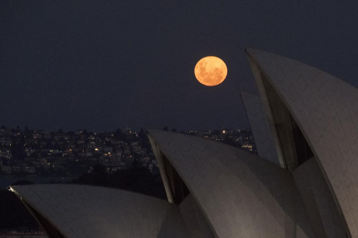 The supermoon rises behind the sails of the Sydney opera House, in Australia, on April 27, 2021.