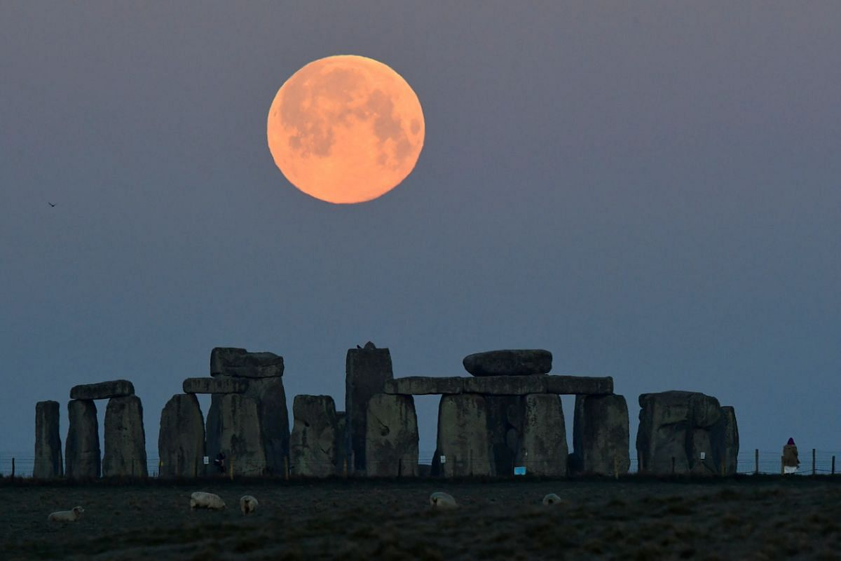 A person watches as the supermoon sets behind Stonehenge stone circle near Amesbury, Britain, on April 27, 2021.