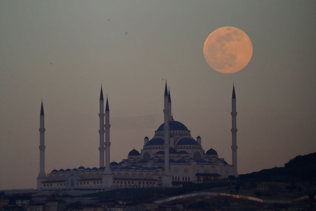The supermoon rises above the Camlica Mosque in Istanbul, Turkey, on April 26, 2021.