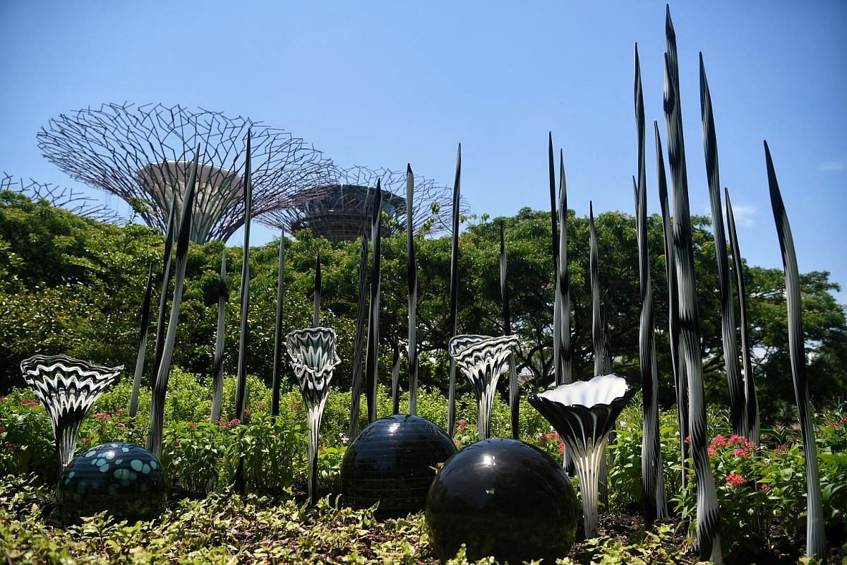 Gardens by the Bay's (from far left) Mr Gary Chua and Ms Marziah Omar, and Mr Michael Lee, the exhibition's organising committee chairman, in the Flower Dome, which incorporates three Chihuly works: The White Tower, Neodymium Reeds, and Erbium Reeds