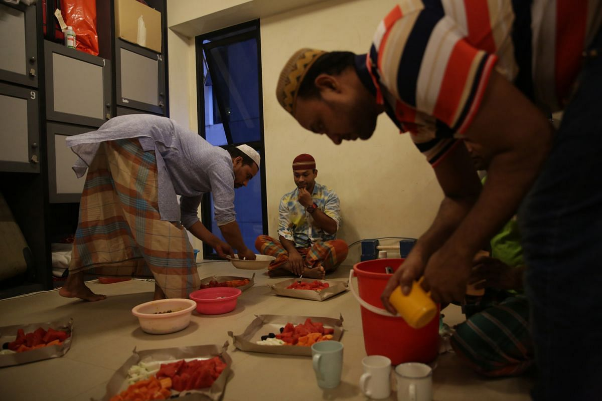 Mr Rafique getting ready for iftar, as his fellow Muslim room-mates prepare fruit platters of  dates, watermelon, papaya and guava with fruit juice drinks.