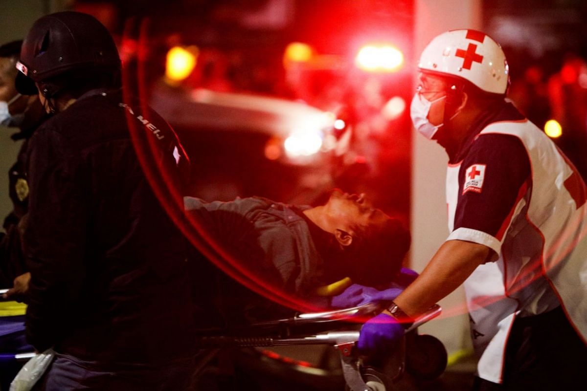 Rescuers transport a casualty on a stretcher at a site where an overpass for a metro partially collapsed with train cars on it at Olivos station in Mexico City, Mexico, May 3, 2021.