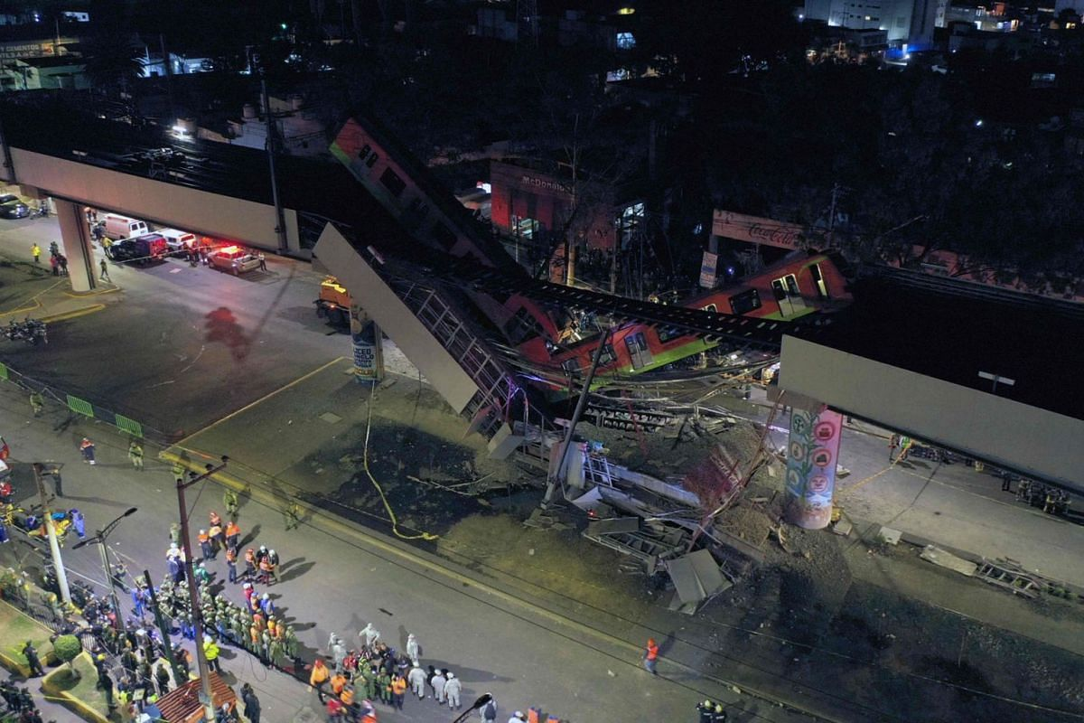 An aerial view shows rescue workers at the site of a metro train accident after an overpass for a metro partially collapsed in Mexico City on May 3, 2021.