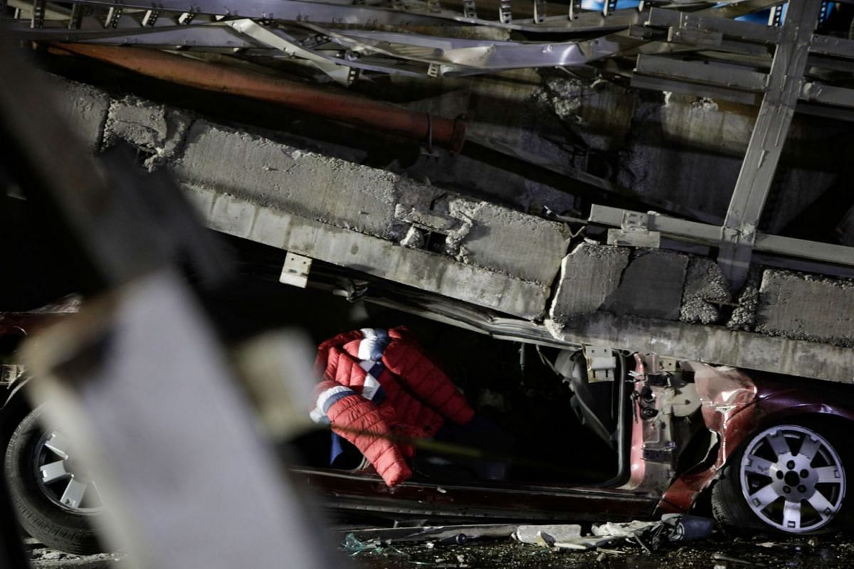 A car is seen trapped under an overpass for a metro that partially collapsed with train cars on it at Olivos station in Mexico City, Mexico, May 4, 2021.