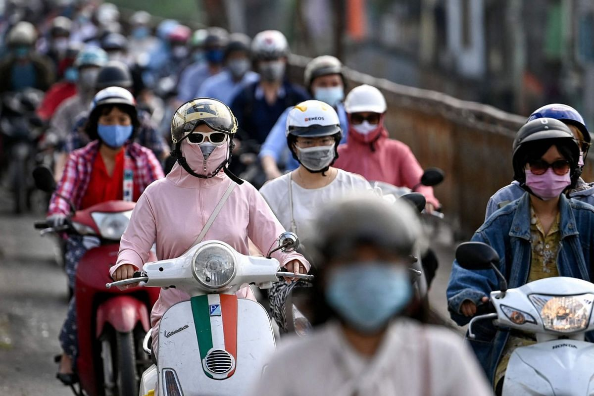 Morning commuters wearing face masks, amidst concerns about the Covid-19 coronavirus, ride past in Hanoi on May 4, 2021.
