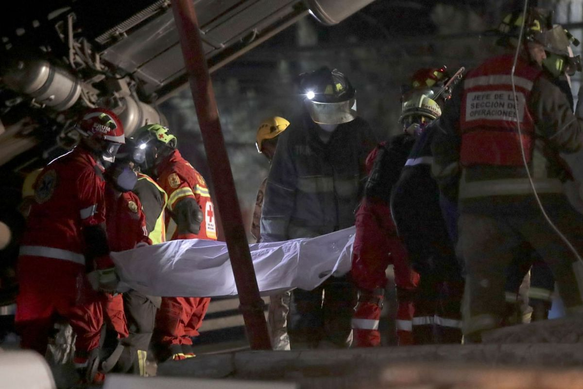 Rescue workers carry a body at a site where an overpass for a metro partially collapsed with train cars on it at Olivos station in Mexico City, Mexico May 4, 2021.