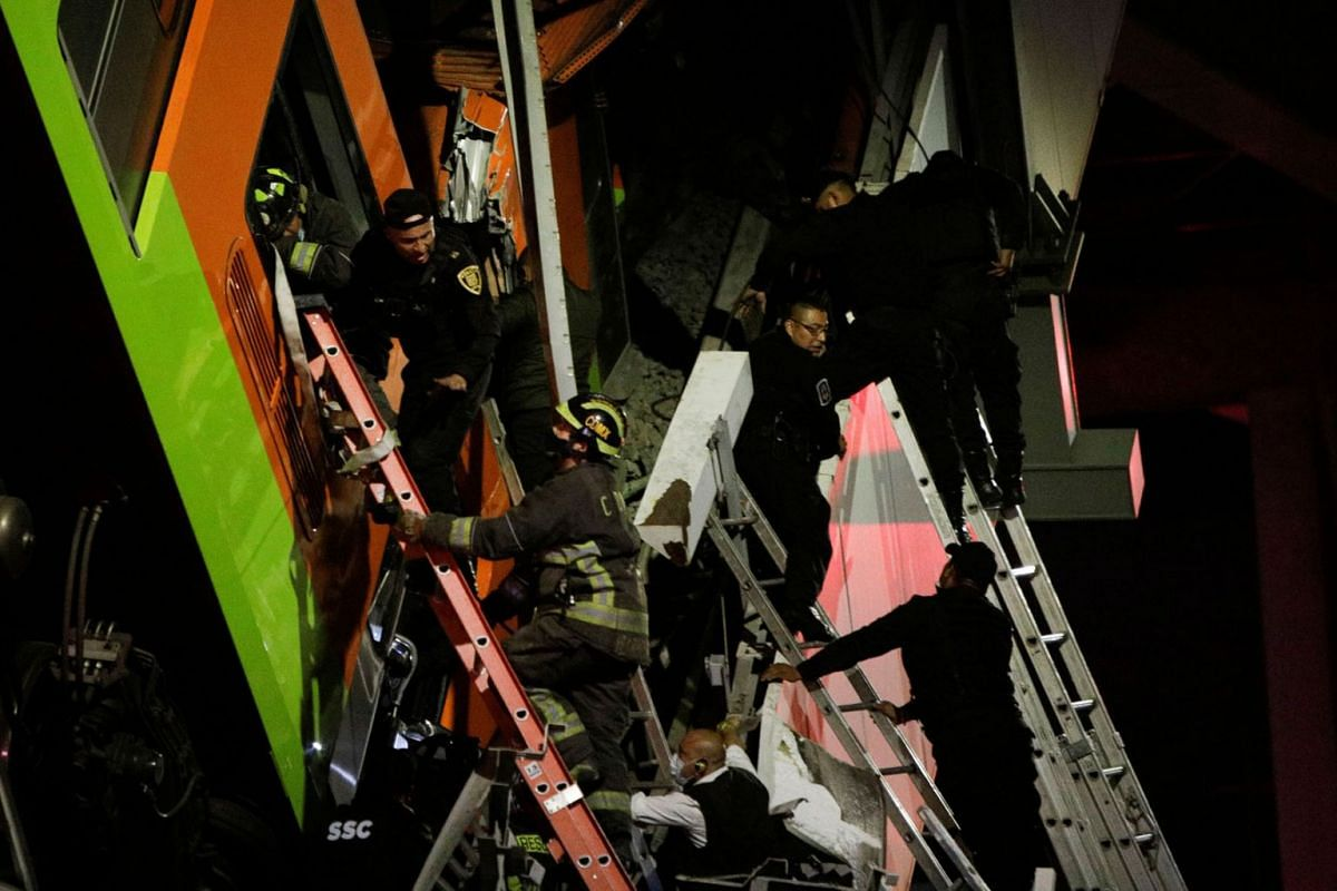 Rescuers work at a site where an overpass for a metro partially collapsed with train cars on it at Olivos station in Mexico City, Mexico, May 3, 2021.
