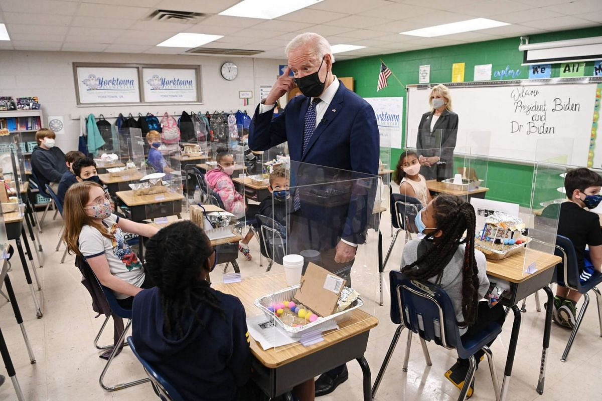 US President Joe Biden points to his hair after a student told him she wanted to be a hairstylist when she grows up, as he and First Lady Jill Biden (R) visit Yorktown Elementary School in Yorktown, Virginia on May 3, 2021.