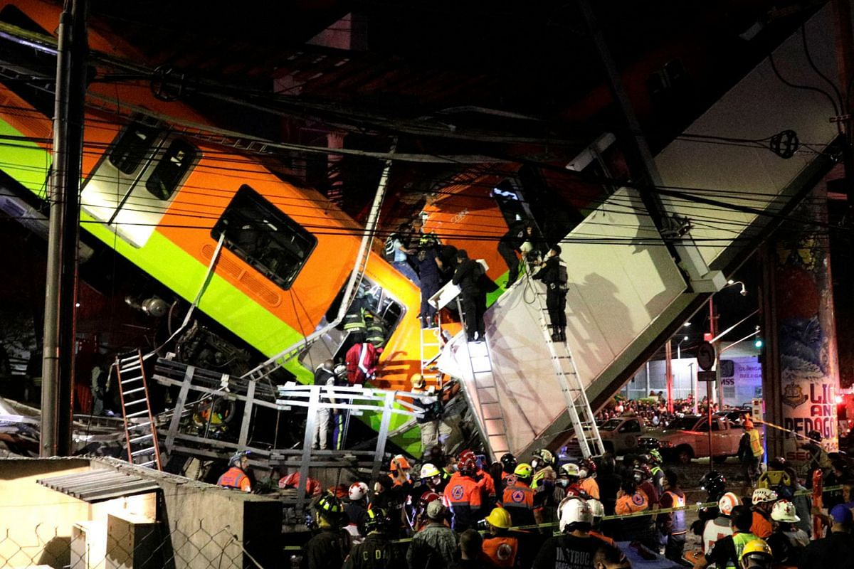 Rescuers work use ladders to reach the derailed train  cars at Olivos station in Mexico City, Mexico May 3, 2021.