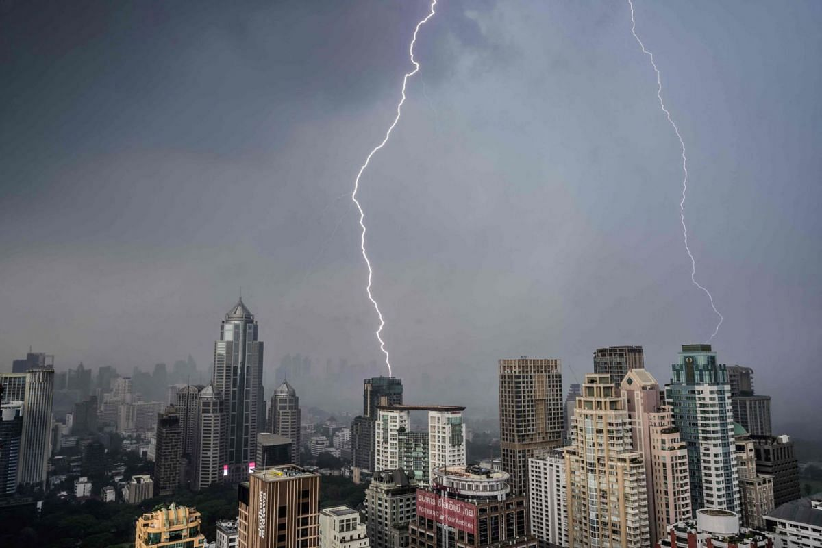 Lightning bolts strike buildings during a thunderstorm in Bangkok on May 3, 2021.