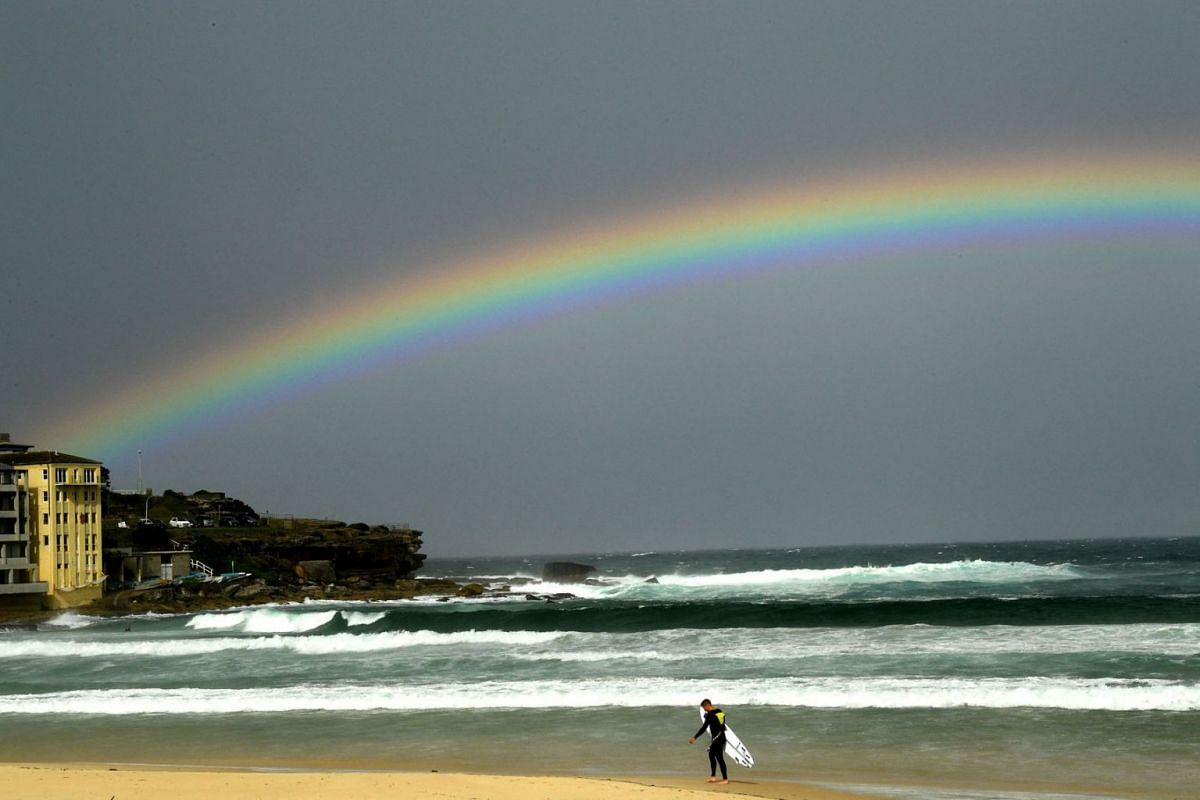 A rainbow is seen as it rains over the Bondi Beach in Sydney on May 6, 2021.