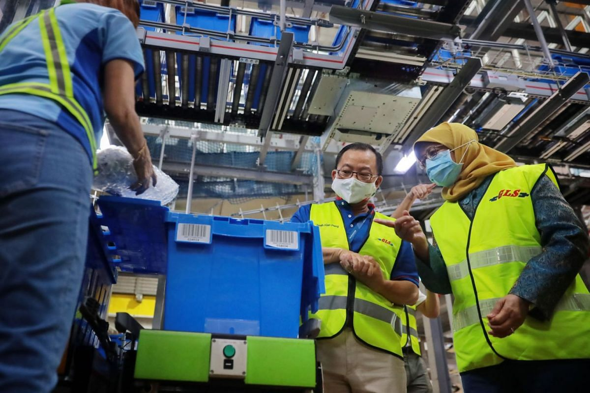 President Halimah Yacob visiting FairPrice Group's supply chain business unit at Benoi Distribution Centre in Joo Koon on 6 May 2021, accompanied by FairPrice group chief executive Seah Kian Peng.