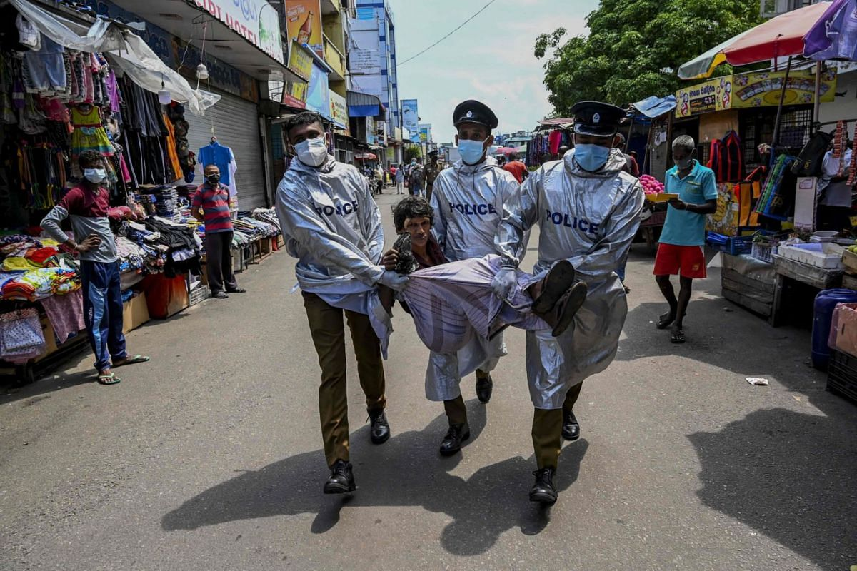 Sri Lankan policemen wearing PPE remove a man arrested in the capital Colombo on May 7, 2021, for not wearing a face mask.