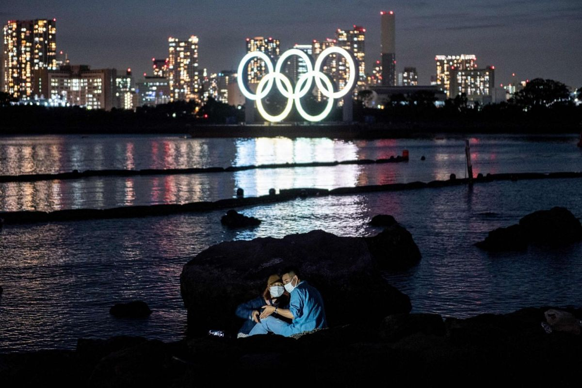 A couple pose for pictures before the lit Olympic rings at the Odaiba waterfront in Tokyo on May 6, 2021.