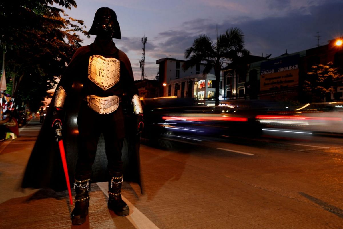 A person in costume stands at the side of a road during a gathering of the supporters of anti-government protest leaders arrested and charged with lese majeste, waiting for their release in Bangkok, Thailand, May 11, 2021.