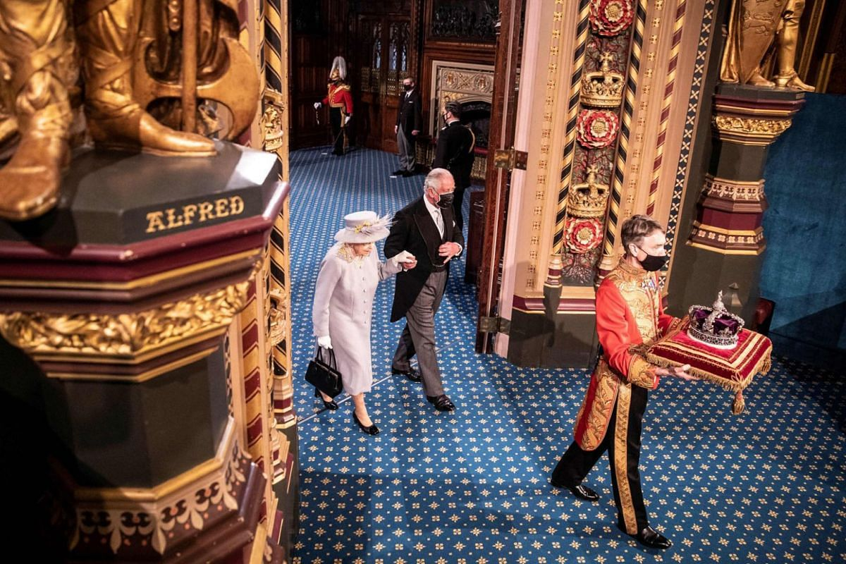 Britain's Queen Elizabeth II and Britain's Prince Charles, Prince of Wales walk behind the Imperial State Crown as they process through the Royal Gallery, after the Queen's Speech, during the State Opening of Parliament at the Houses of Parliament i