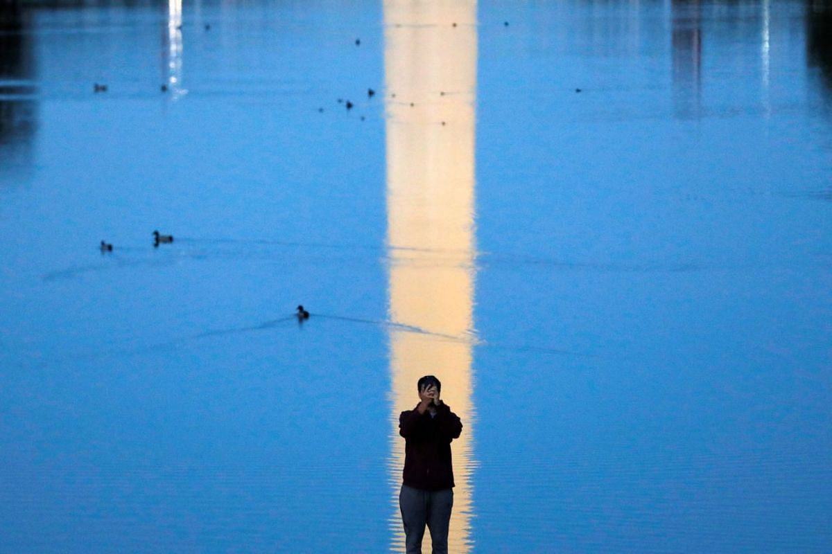 A person uses a cell phone as the Washington Monument is reflected in the Lincoln Memorial Reflecting Pool in Washington, D.C., U.S., May 10, 2021.
