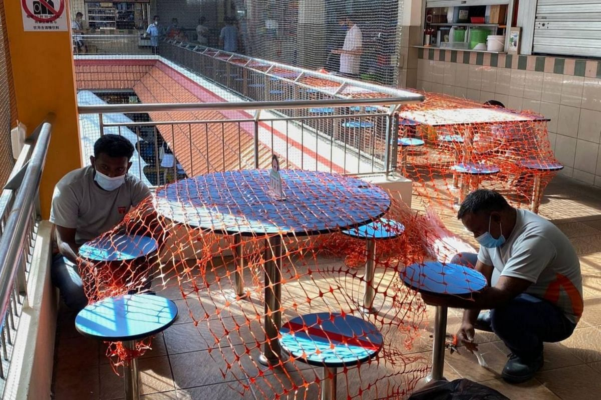 Workers fencing off tables and chairs at Golden Mile Food Centre on May 15, 2021.