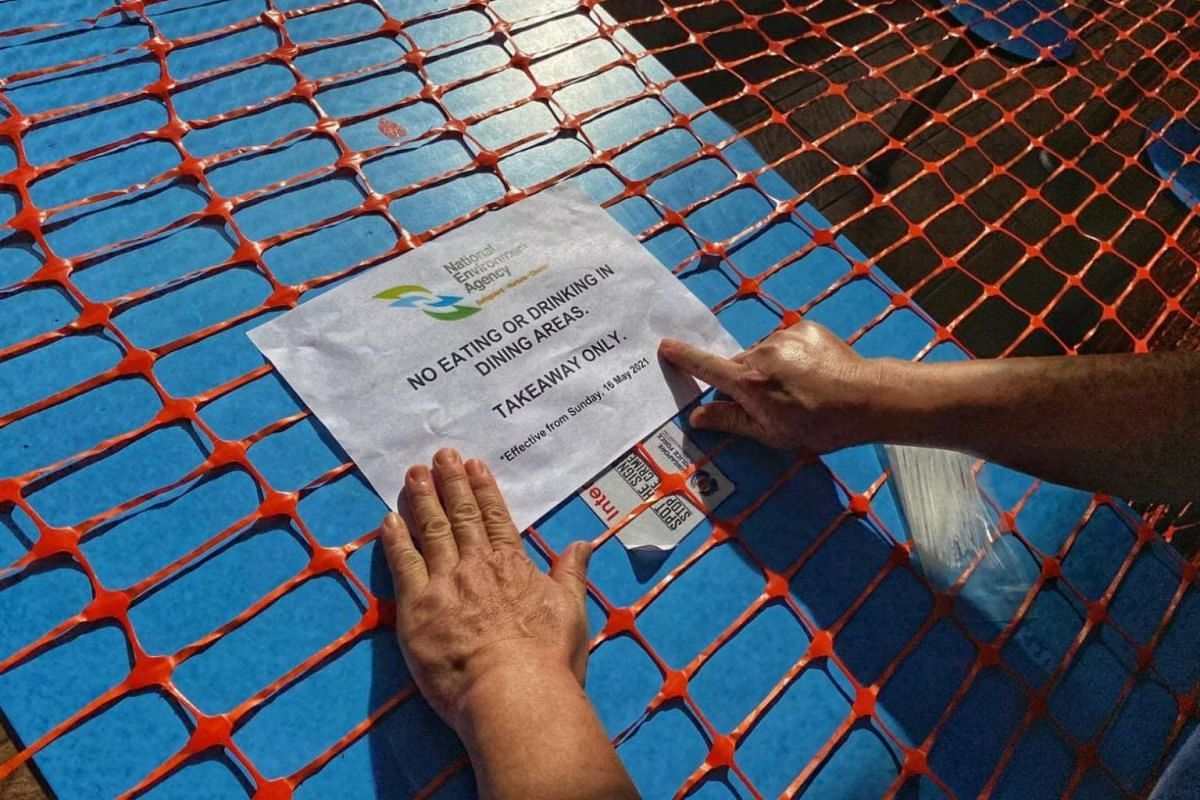 A worker pastes a National Environment Agency notice on a table at Golden Mile Food Centre on May 15, 2021.
