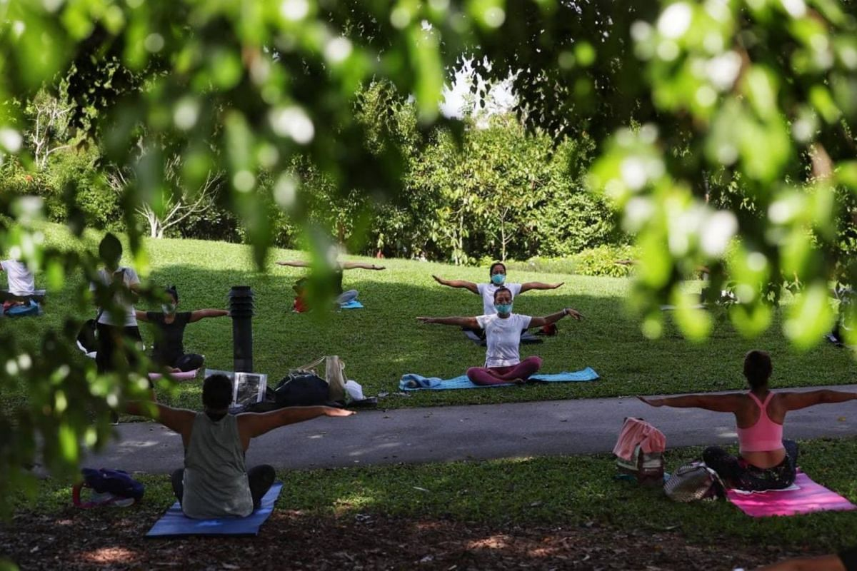 Volunteers conduct a yoga session for foreign domestic workers at Singapore Botanic Gardens on May 16, 2021.