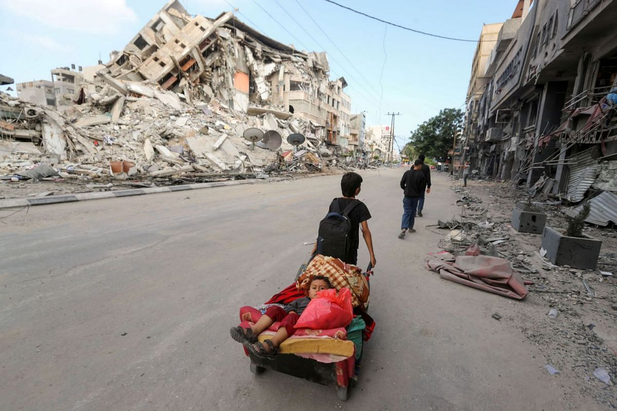 A Palestinian boy pulls a cart carrying his brother and their belongings as they flee their home during Israeli air and artillery strikes, near the site of a tower building destroyed in earlier strikes in Gaza City, May 14, 2021.