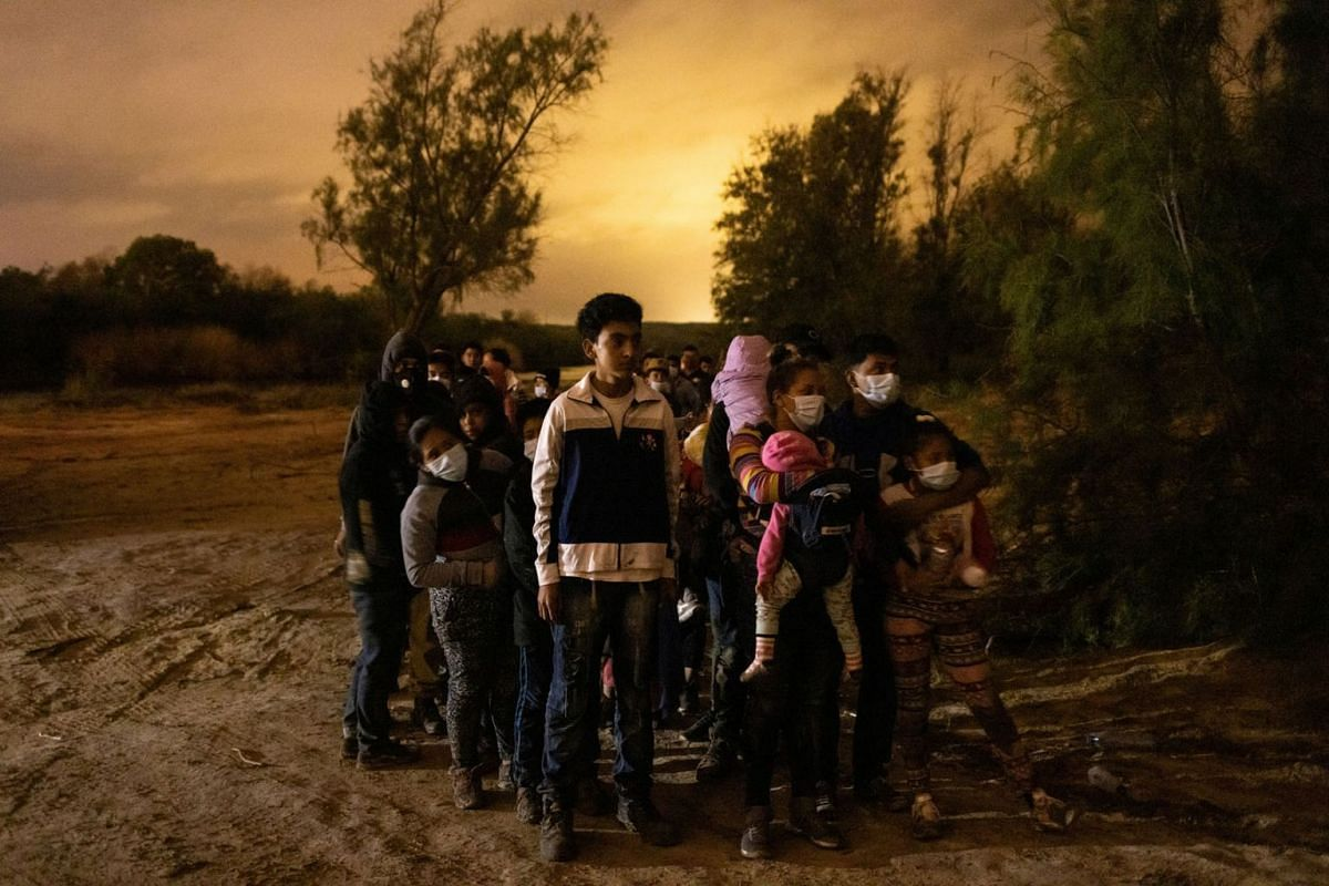 Asylum seeking migrants from Central America line up to be escorted to the main road by the Texas Army National Guard after crossing the Rio Grande river into the United States from Mexico, in Roma, Texas, U.S., May 15, 2021.