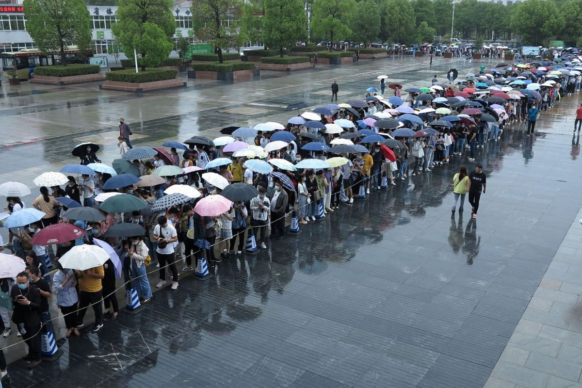People queue in the rain to get vaccinated against the coronavirus disease, outside a vaccination site in Fuyang, Anhui province, China, May 15, 2021.