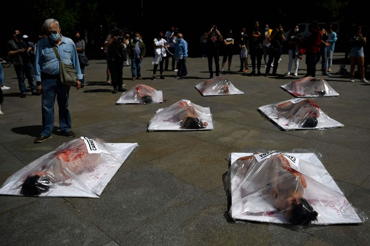 """AnimaNaturalis animal rights activists covered in red paint lie in giant meat packages reading """"Human meat"""" during a demonstration against meat consumption in Madrid on May 16, 2021."""