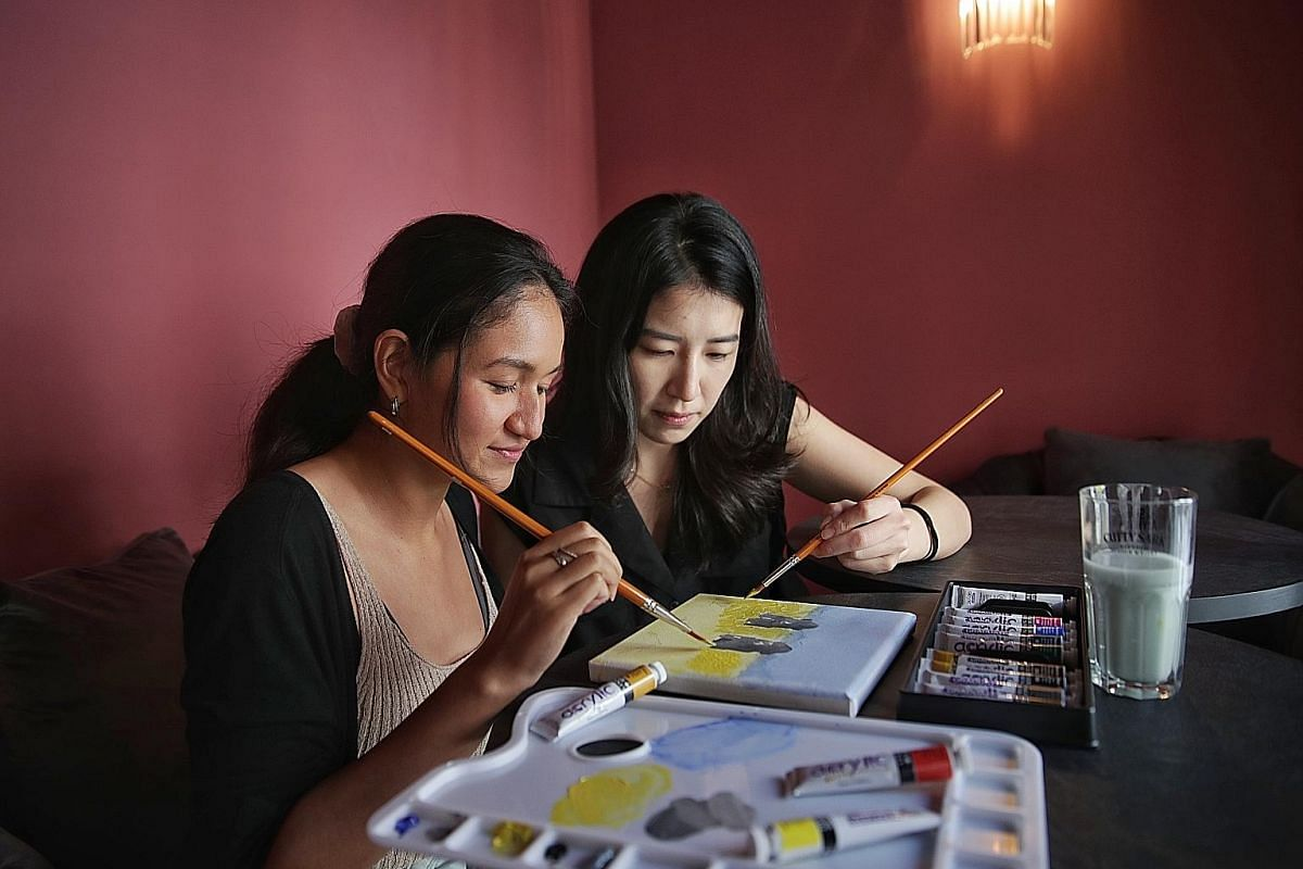 Part-time art instructor Irene Lee (above right) guiding Straits Times writer Sarah Stanley (left) with her painting. (Below) Sool Sool Jeju Art Cafe's seven types of craft beers named after South Korean cities and districts. The wax figure of South
