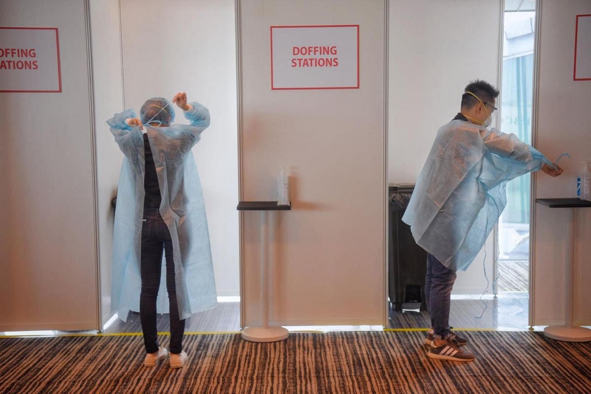 Changi Airport staff taking off their personal protective equipment at a doffing station before proceeding to the rest area at Zone 1 of Terminal 3 on May 24, 2021.