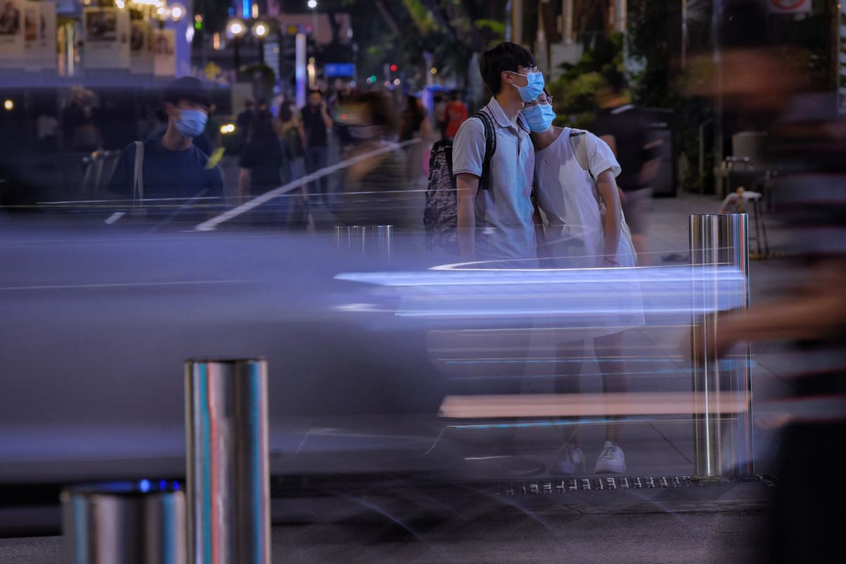 An exhausted shopper leaning on her companion as they wait to cross a traffic junction in Orchard Road on May 21, 2021.