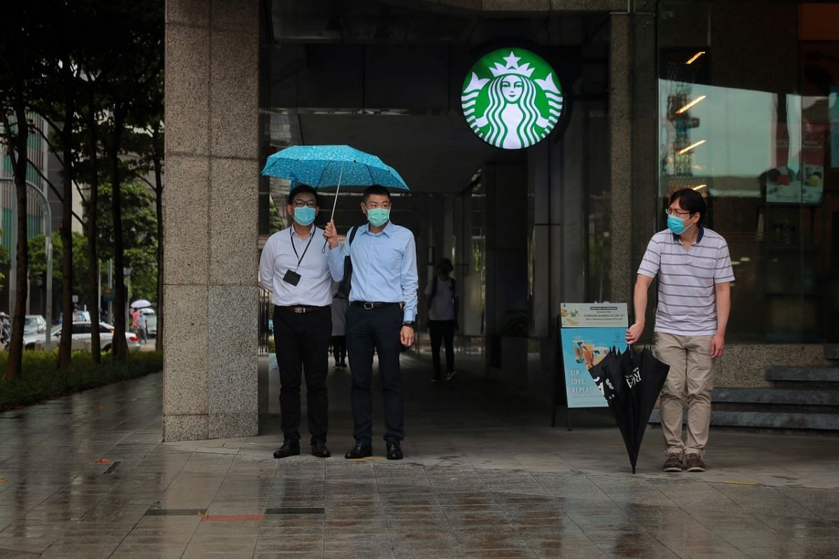 Office workers sharing an umbrella on a wet afternoon on May 17 as they wait for the downpour to ease in Cross Street.