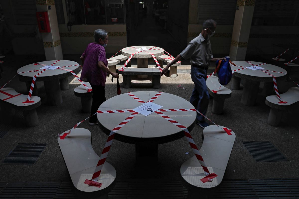 An elderly couple weaving their way across taped seats and tables at Block 448, Clementi Market and Food Centre, on May 16, 2021.