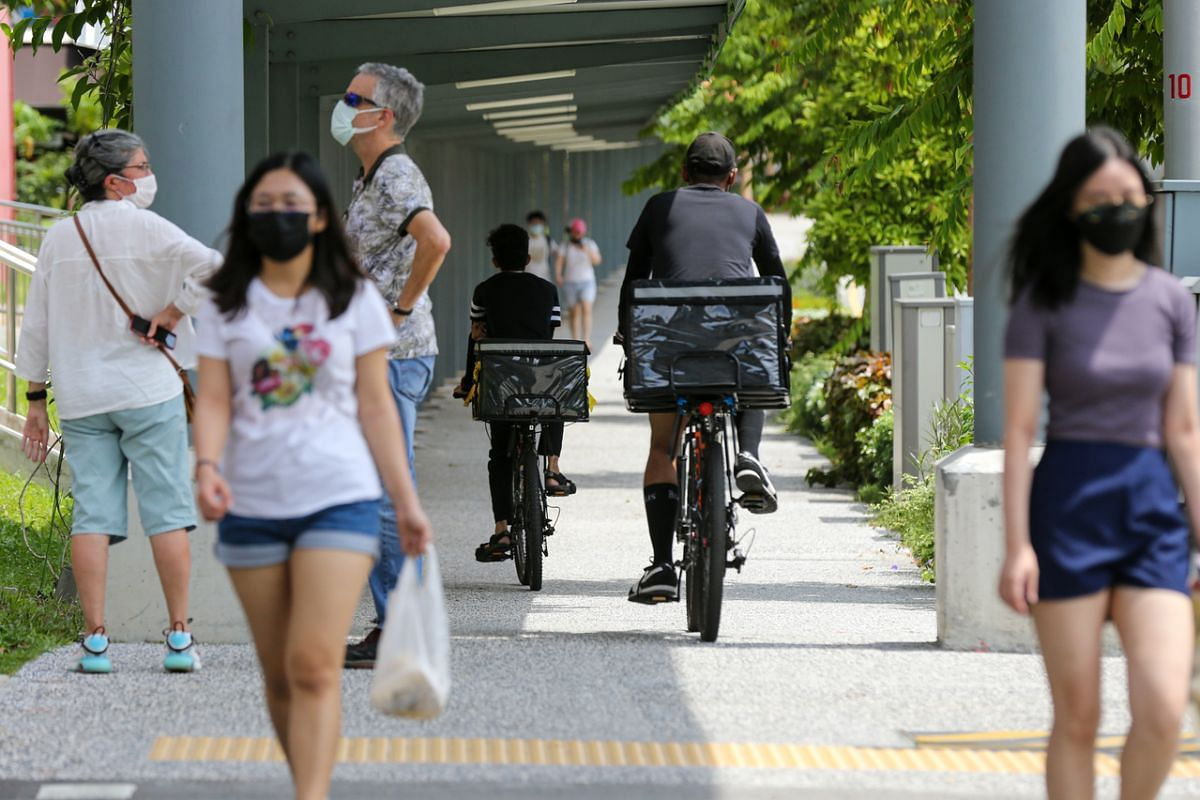 Two food delivery riders cycling along a sheltered walkway on May 26, 2021.