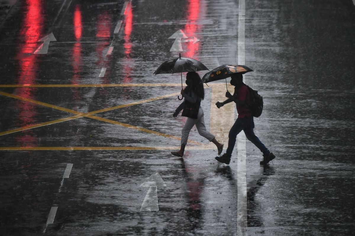 Jaywalkers matching each other stride for stride during a downpour in Newton Road on May 18, 2021.