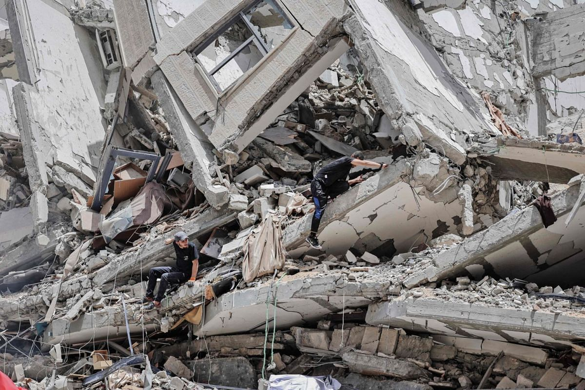 Palestinian workers clear the rubble and debris in Gaza City's al-Rimal neighbourhood, which was targeted by Israeli strikes during the recent confrontation between Hamas and Israel, on June 8, 2021.