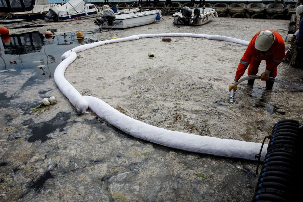A worker cleans plague of sea snot, a thick slimy layer of the organic matter also known as marine mucilage, that has spread through the Sea of Marmara and which poses a threat to marine life and the fishing industry, on the shores of Istanbul, Turke