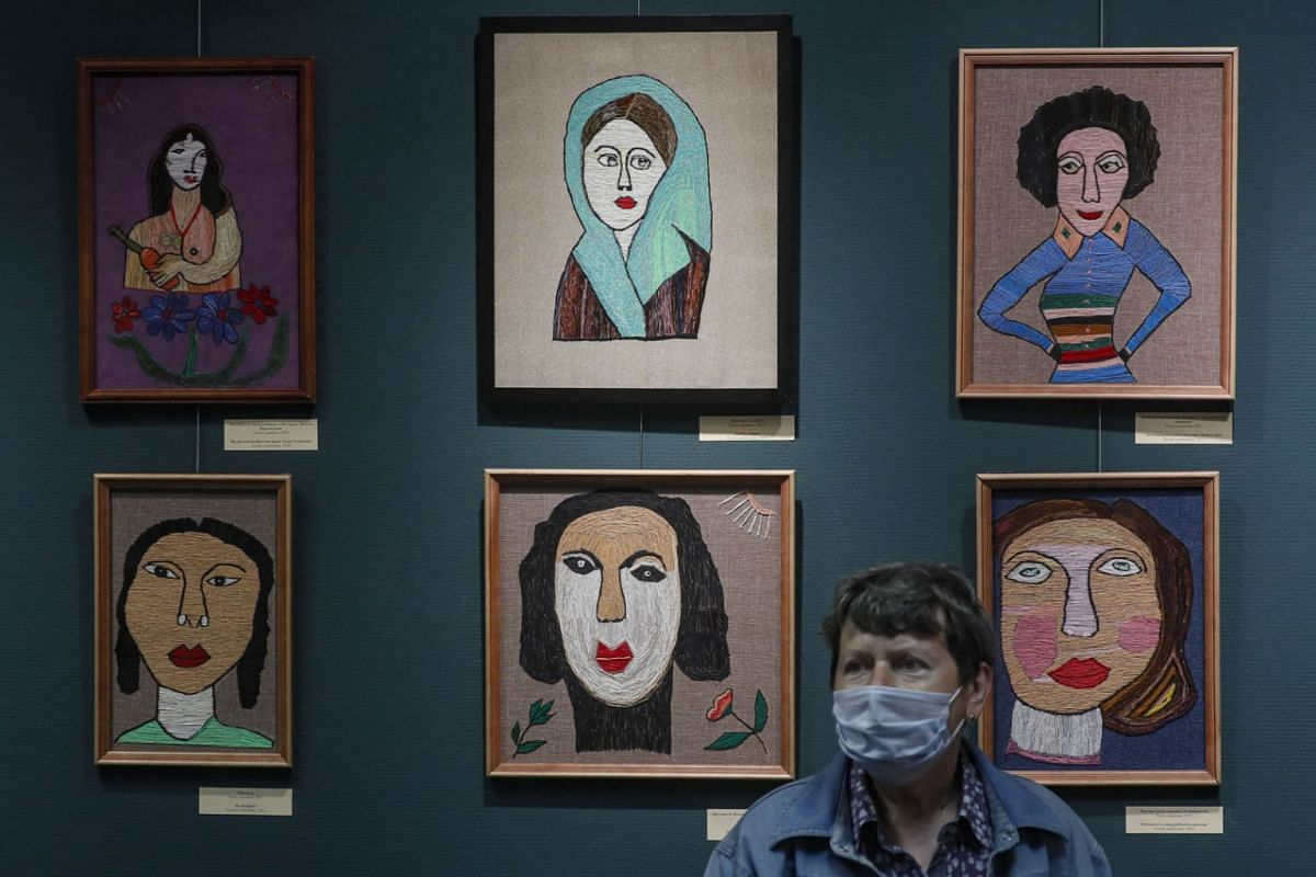 A visitor passes by artworks by the 83-year-old artist Julia Aleshicheva, aka Miss Julia, created in embroidery technique, on display in the exhibition 'The Girl from 1938: Embroidery Life-Long' at the Museum of Russian Lubok and Naive Art in Moscow,