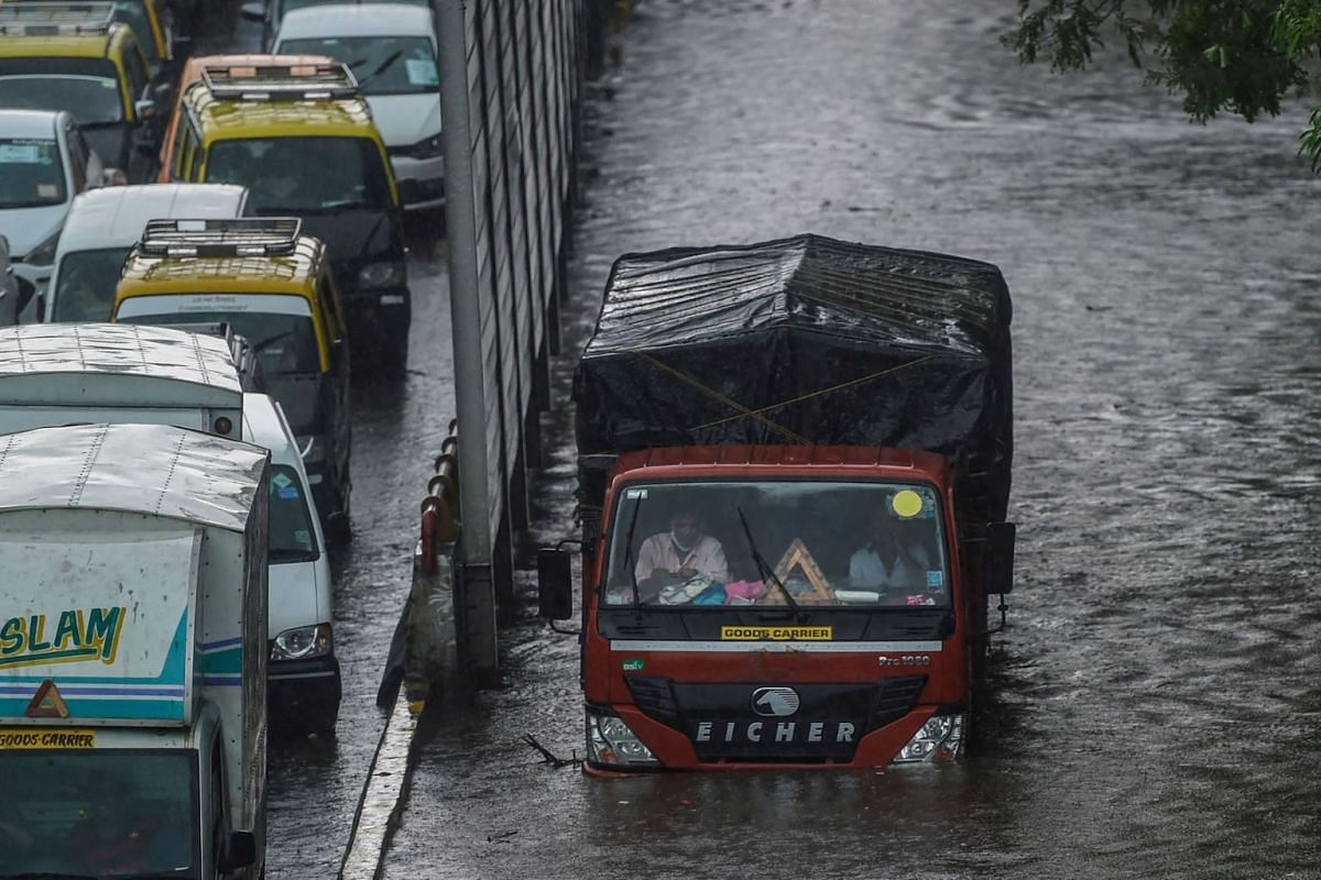 Vehicles navigate through flooded roads following heavy monsoon rains in Mumbai on June 9, 2021.