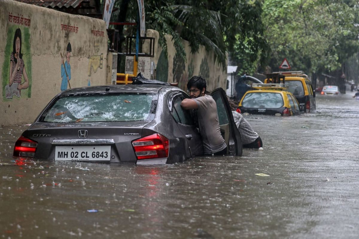 People push a car in a flooded street during heavy rain in Mumbai, India, on June 9, 2021. Vehicular movements were affected and local trains were delayed due to the downpour in the city.