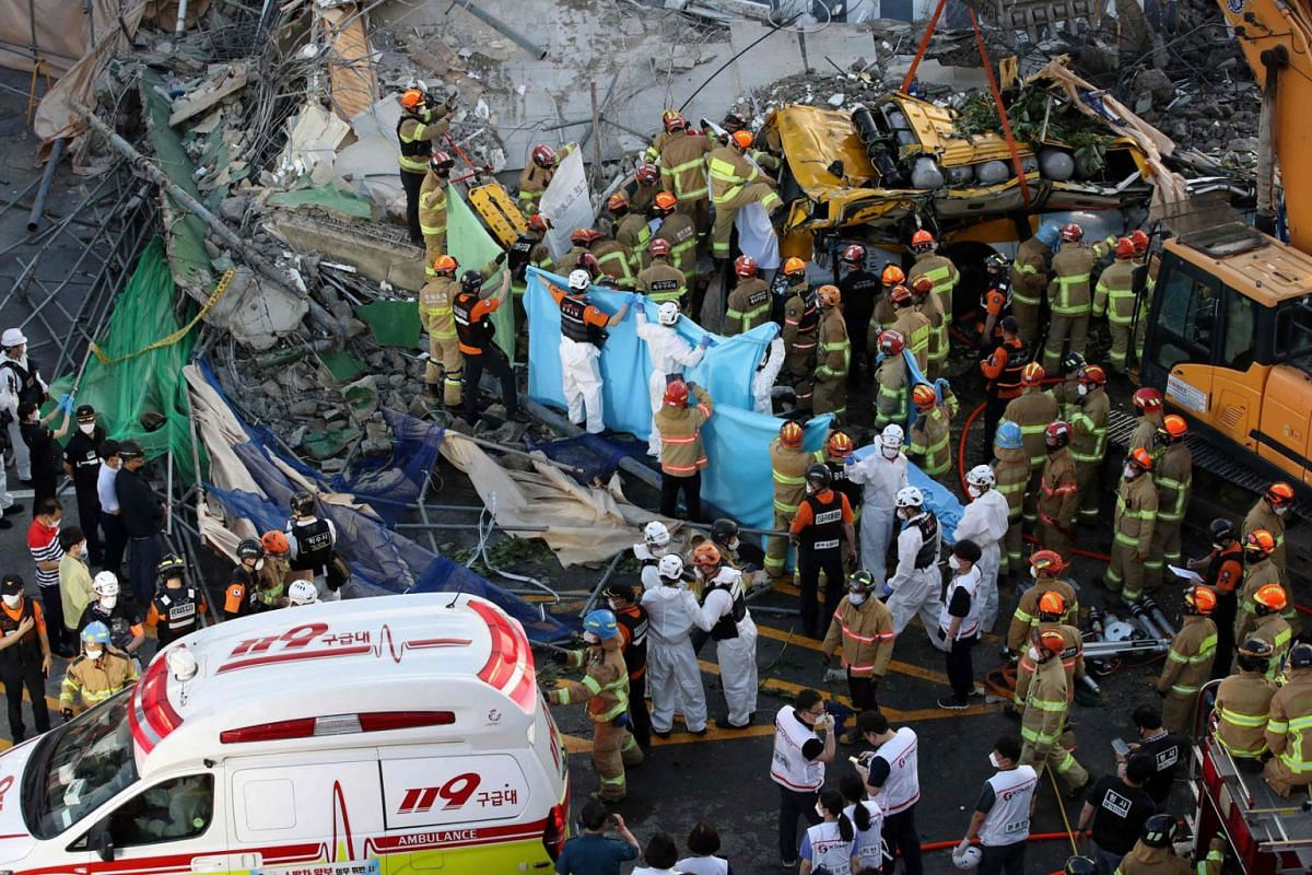 South Korean rescue workers search for possible survivors from the debris of a collapsed building in Gwangju on June 9, 2021.